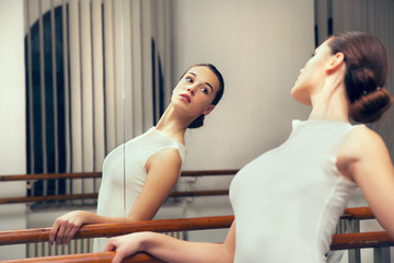 Ballerina posing, reflection in the mirror on the background