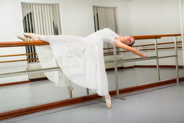 Classic ballet dancer in white tutu posing next to handle bar