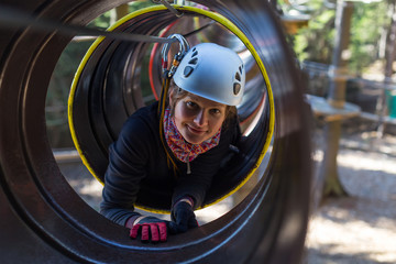 young woman climbing in a barrel