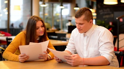 happy couple talk in cafe - couple read papers (contract)