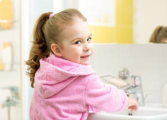 little girl washing in bathroom