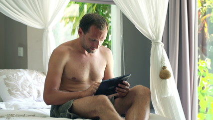 Young man with tablet computer lying on bed at home