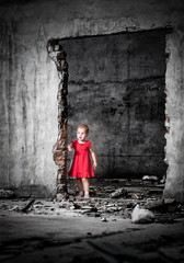 Neglected little girl in the middle of demolished building