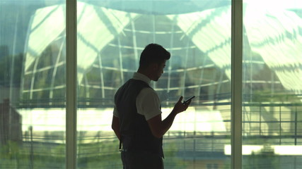 The businessman call by mobile phone by the glass attic window