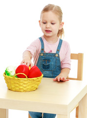 Little girl lying disassembled in a fruit basket.