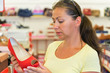woman chooses red shoes in a store before buying