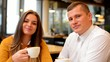 happy couple drink coffee and smiles in cafe -closeup