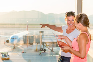 girl shows her friend a plane before take-off