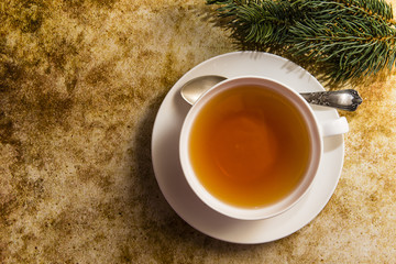 Cup of tea with green branches decoration on colorful background
