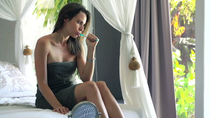 Attractive young woman brushing her teeth in bedroom