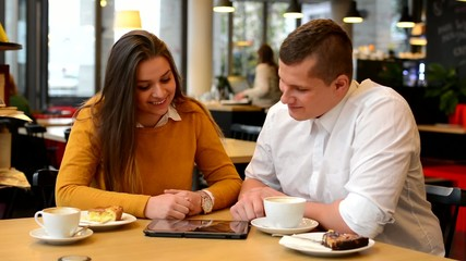 happy couple works on tablet in cafe - coffee and cake