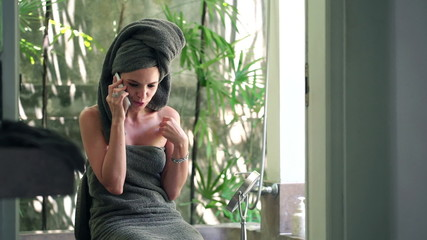 Young pretty woman talking on cellphone in the bathroom