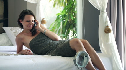 Young pretty woman talking on cellphone in the bedroom