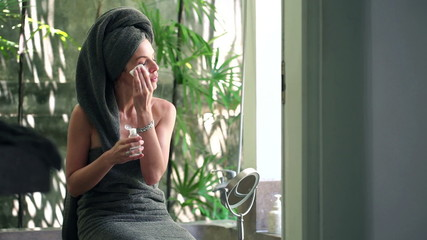Woman cleaning face with cotton swab in bathroom