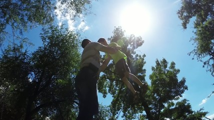 Dad throws son in his arms in the park, Slow Motion 1