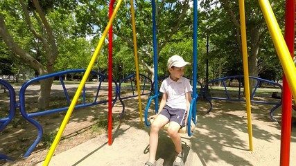 boy ride on a swing in the playground, slow motion 2