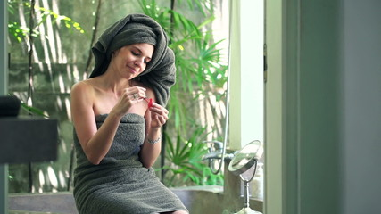 Attractive young woman painting her nails in bathroom