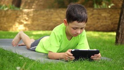 little boy plays the tablet in the park, dolly 4