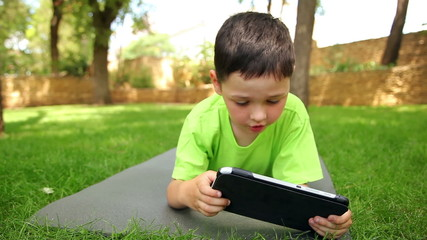 little boy plays the tablet in the park, dolly