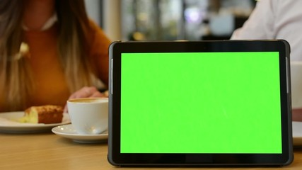 tablet green screen - couple eat and drink in cafe in background