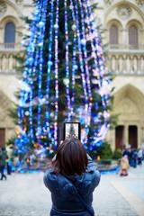 Asian tourist in Paris taking photo of Christmas tree