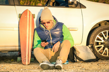 Young hipster man with smartphone sitting next his car