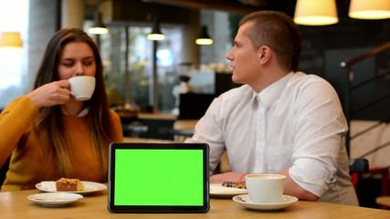tablet green screen - happy couple talk, eat and drink in cafe