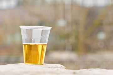 Ein Becher - halb voll mit Bier - steht auf einer Mauer