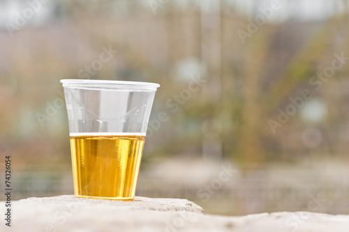 Leinwandbild Motiv Ein Becher - halb voll mit Bier - steht auf einer Mauer