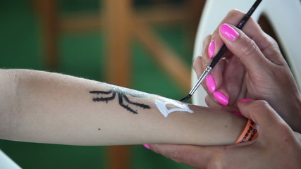 woman paints a spider on the hand of a boy 1