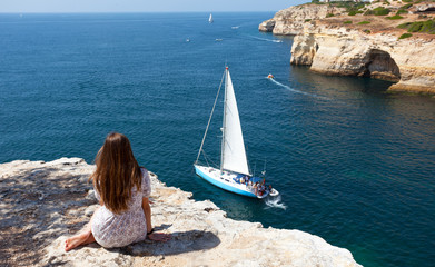 girl sits on the rock and looks at yachts at the ocean