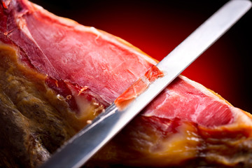 Jamon serrano. Traditional spanish ham. Slicing hamon iberico