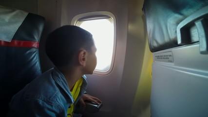little boy looks in the window of the plane