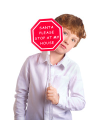Boy holding christmas sign asking Santa to come by. Isolated on