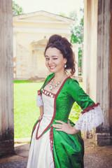 Beautiful woman in green medieval dress winking