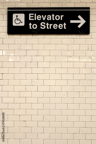 Foto op Canvas Treinstation New York City Station subway directional sign on tile wall.