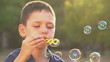 beautiful caucasian boy playing with soap bubbles in the park
