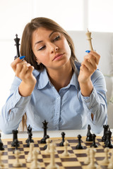 Young Pretty Businesswoman With Chess Pieces