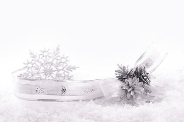 Nicely curved ribbon, stars and silver cones on snow