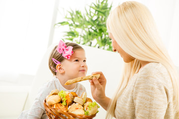 Young Mom Feeds Her Daughter With Pastries