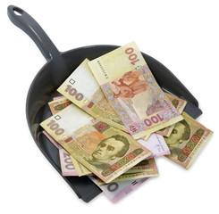 Dustpan with ukrainian  hryvnias. Inflation.