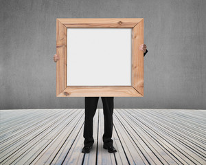 businessman holding blank white board with wooden frame indoors