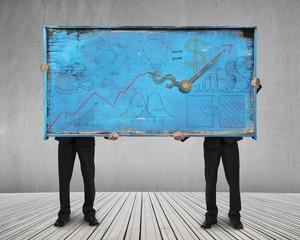 two men holding old blue doodles billboard on wooden floor
