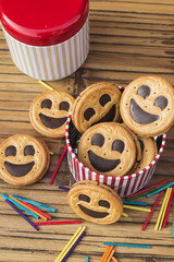 Round smiling chocolate cookies with colourful confetti