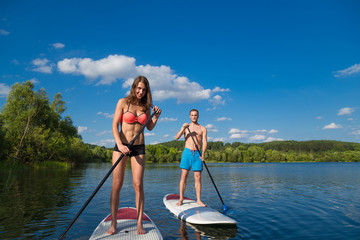Young attractive couple on stand up paddle board in the lake