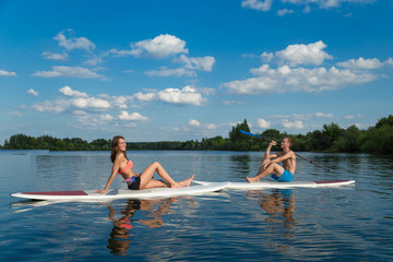 Attractive couple sits on stand up paddle board in the lake