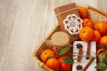basket with Christmas gifts: honey, tangerine and a box with sou