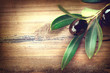 Olive over wood. Olives branch on the wooden table