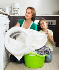 Woman with daughter near washing machine