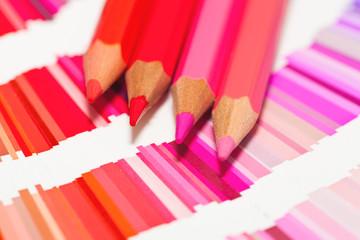 crayons de couleur rose rouge orange sur un nuancier de teintes